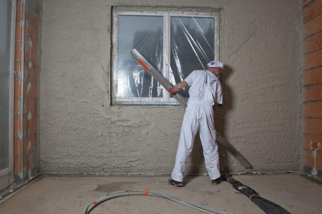 Ściąganie tynku łatą po narzuceniu na ścianę