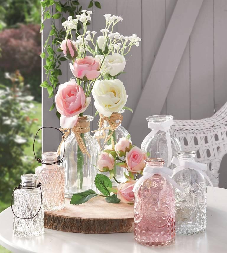 Dekoracja z kwiatów i szklanych wazoników i lampionów